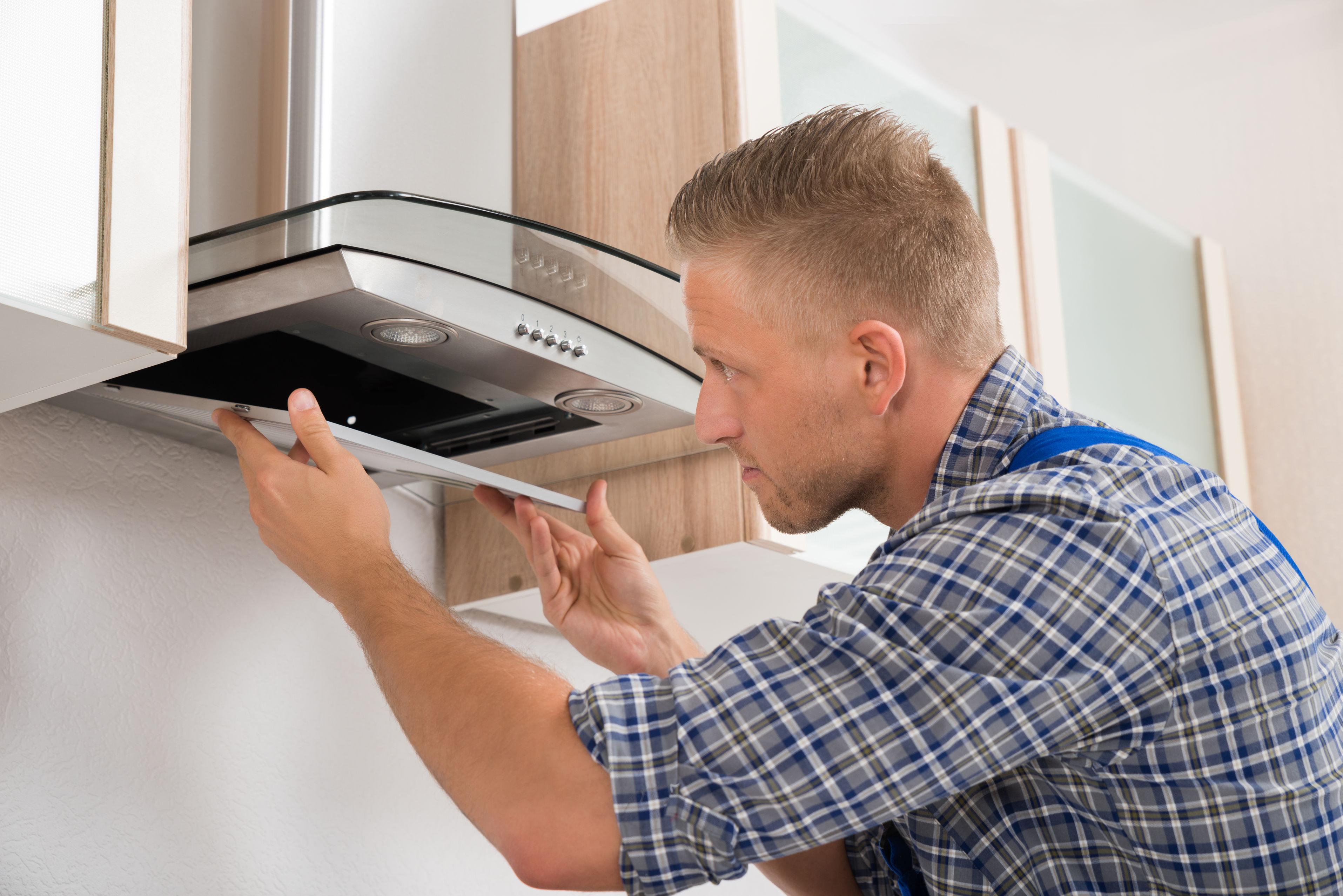 44339942 – young repairman repairing kitchen extractor filter in kitchen room
