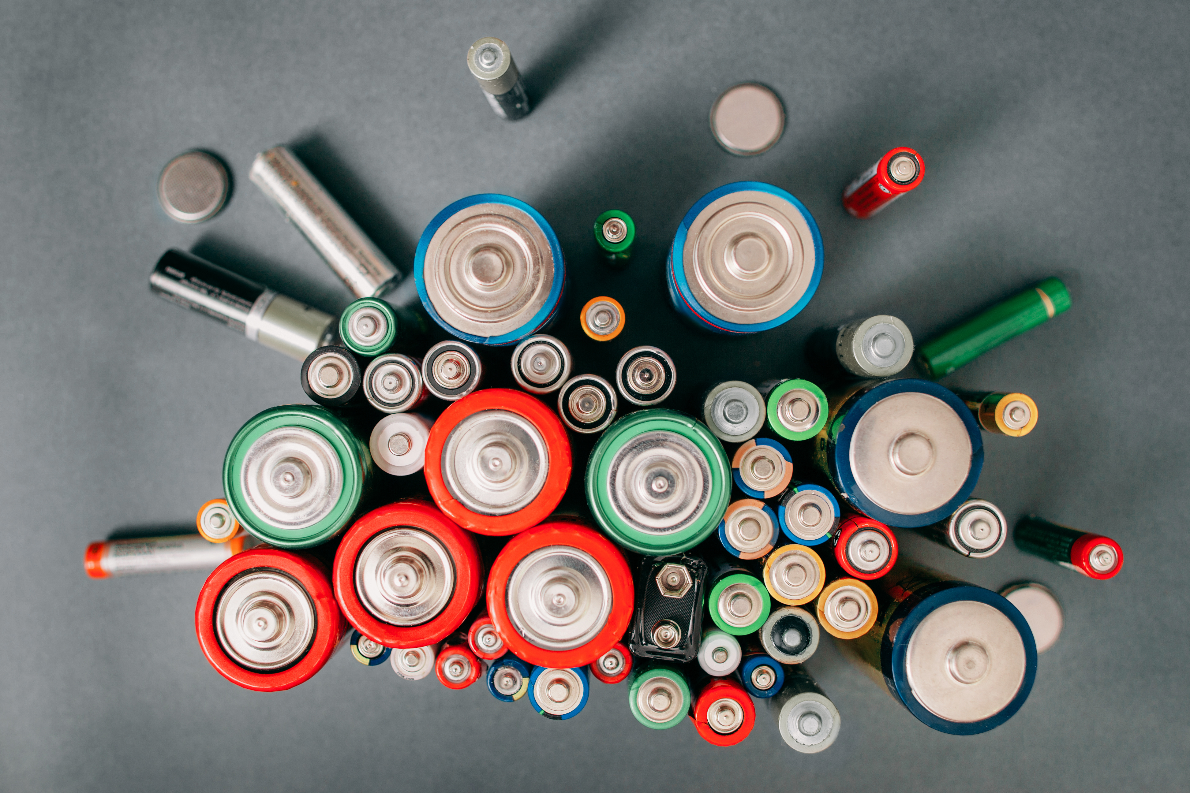 Colorful batteries on gray background, top view